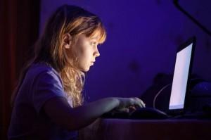 Little blond girl working on laptop in dark room at night